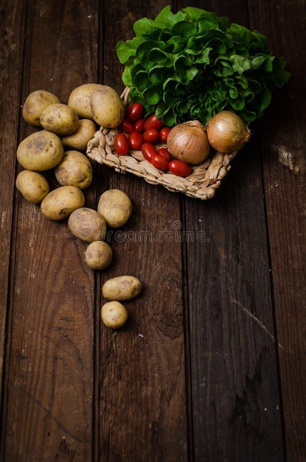 Potatisar med tomater på trägolv royaltyfri fotografi