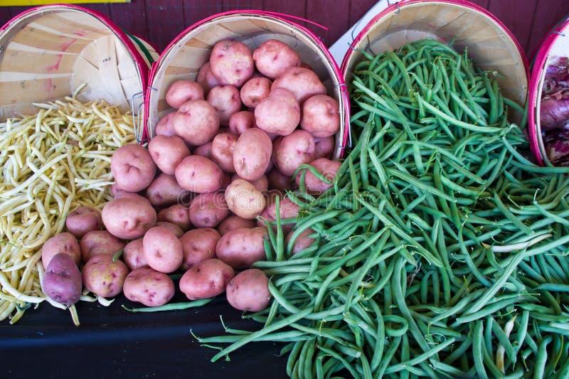 Potatisar och bönor på en horisontalmarknad arkivbild