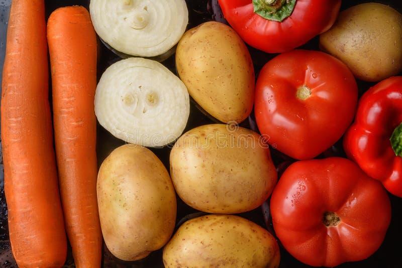 Potatisar, orange morötter, mogna tomater, lökar och röda peppar på en svart bakgrund, bästa sikt arkivbild