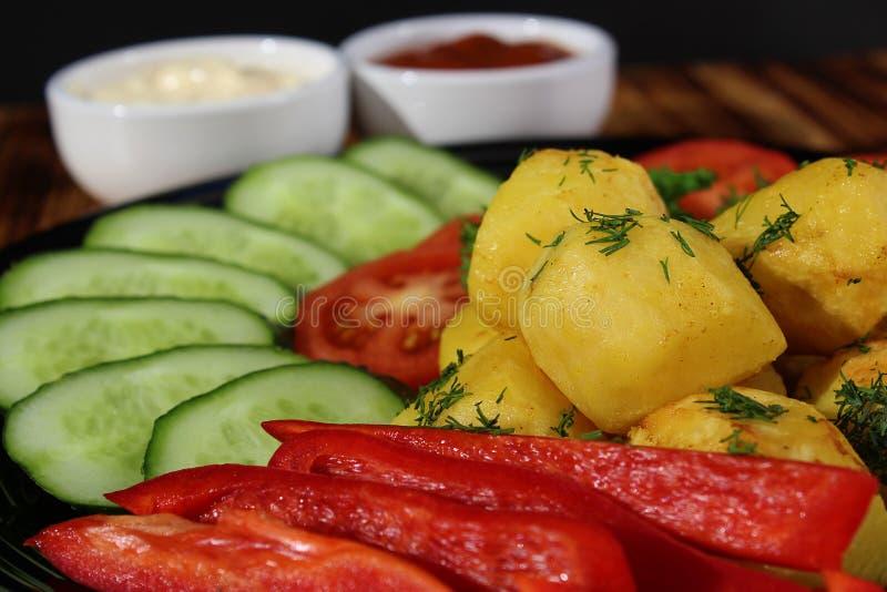 Potatisar som bakas med nya grönsaker arkivbilder