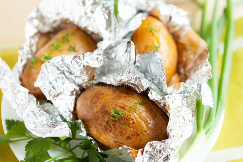Potatisar som in bakas, omkullkastar med örtar royaltyfria bilder