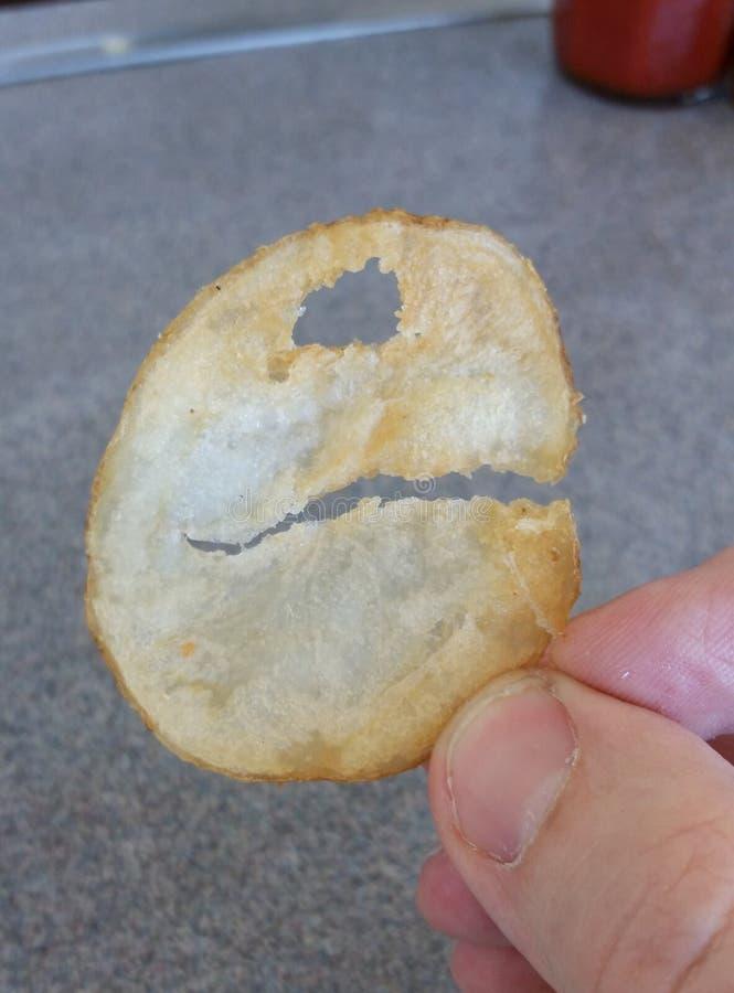 Potatischip som ser som Pac-man arkivfoto