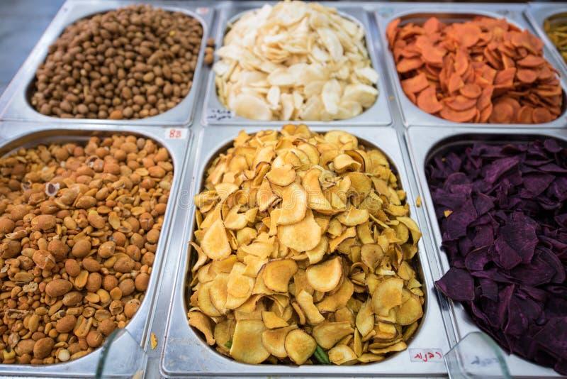 Potatischiper av olika färger och andra mellanmål som är till salu på marknaden royaltyfri fotografi