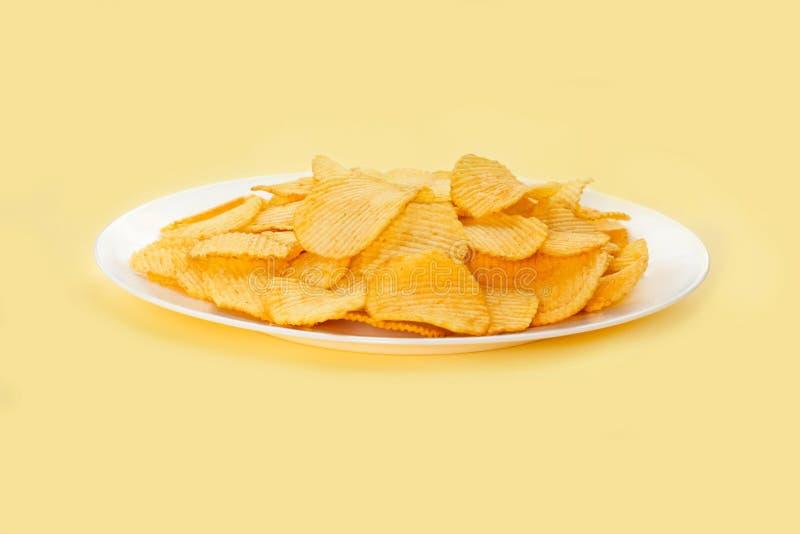 Potatischiper i en vit platta som isoleras på ljus gul bakgrund Skjutit i en studio Slapp fokus royaltyfria foton