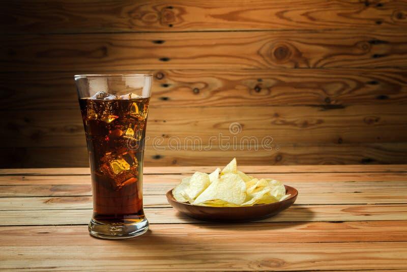 Potatischiper med cola p? en tr?bakgrund royaltyfria foton