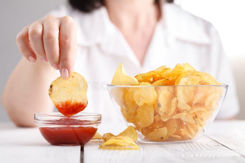 Potatischiper med ketchup, kvinnlig äter skräpmat arkivfoton