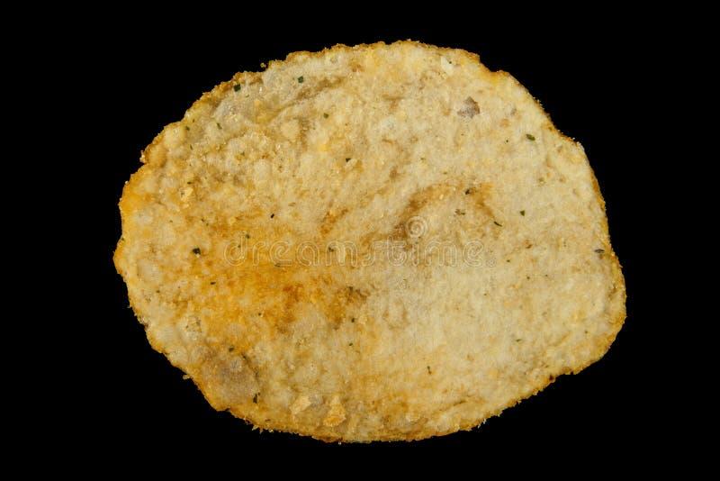 Potatischiper som isoleras på en svart arkivfoto
