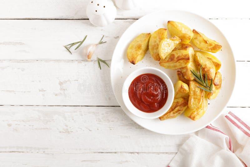 Potatisen bakade och tomatketchup på den vita plattan, träbakgrund royaltyfria bilder