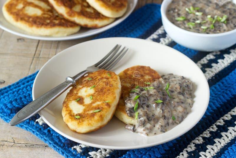 Potatiskotletter eller pannkakor med champinjonsås och salladslökar Lantlig stil royaltyfri bild