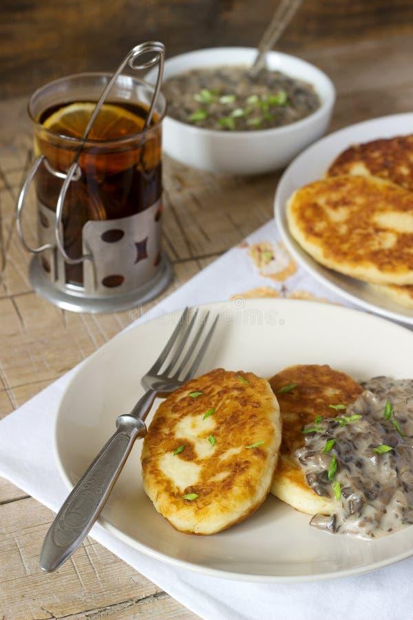 Potatiskotletter eller pannkakor med champinjonsås och salladslökar Lantlig stil arkivbilder