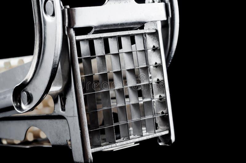 Potatisskärare för att skapa potatispinnar och kuber på en svart bakgrund, isolat royaltyfri fotografi