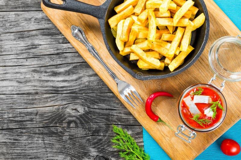 Potatissmåfiskar med stycken av chilipeppar på den vita maträtten och skivorna av den marinerade norska sillen i tomatsås på styc royaltyfria bilder