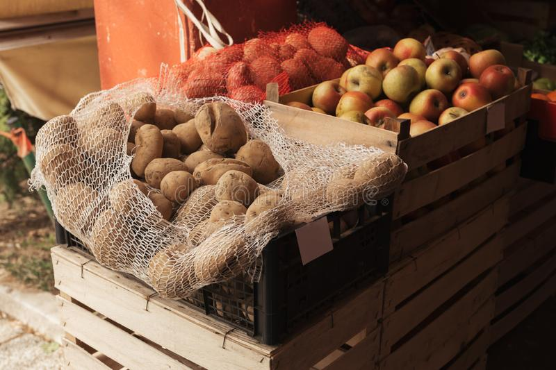 Potato and apples grown locally on outdoor farmer`s market. Placed in wooden crates royalty free stock images