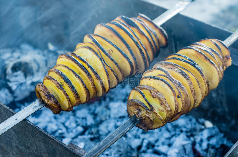 Potato barbecue is fried on charcoal. A shish kebab from yellow potatoes put on a skewer is fried on blue coals royalty free stock photos