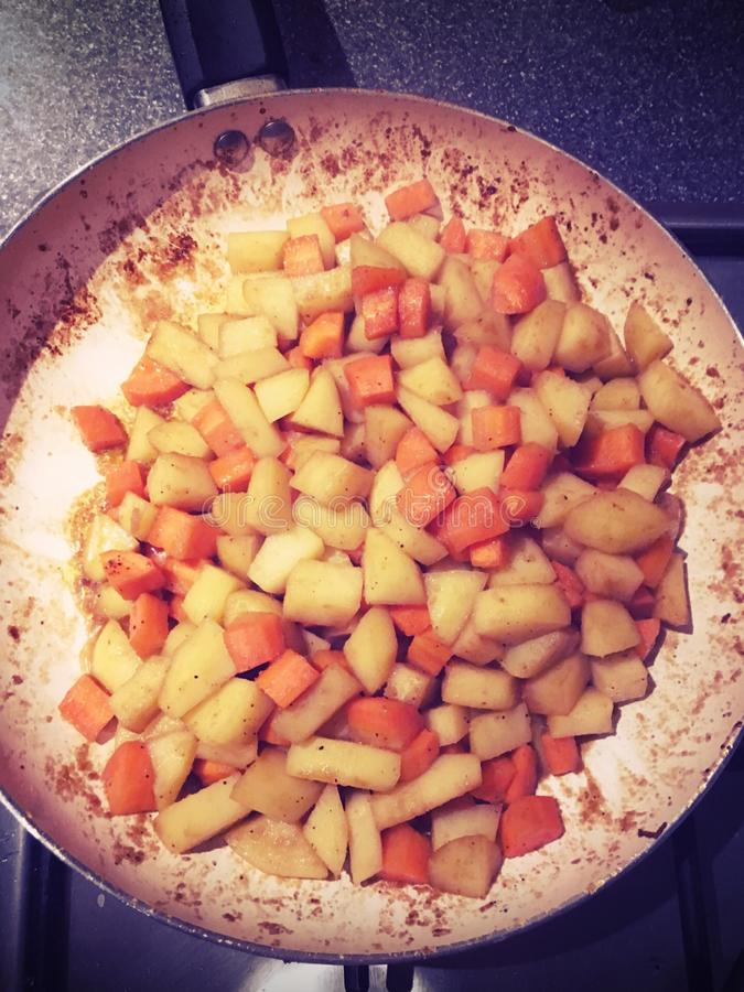Potato and carrot stir fry. Potatoes and carrots in a pan stock photography