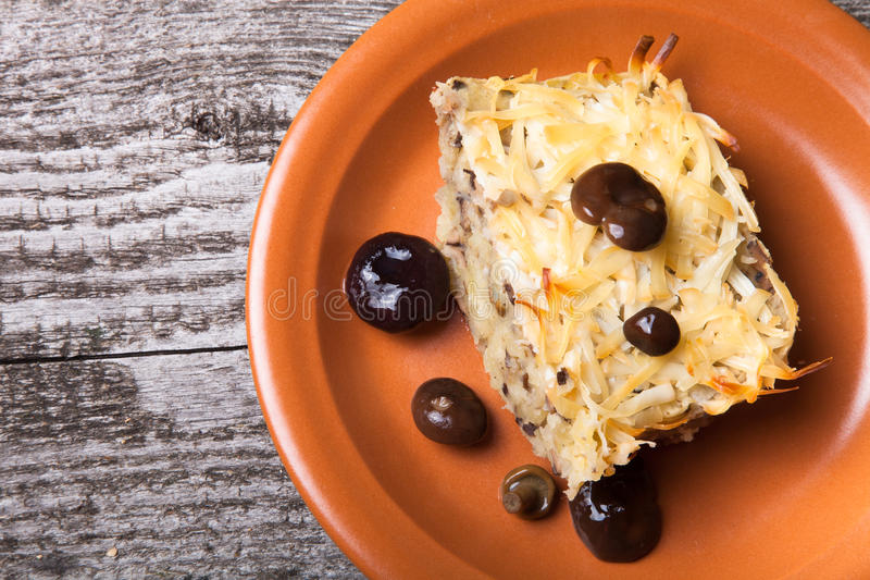 potato casserole with salted mushrooms in a clay plate on old wooden table stock image