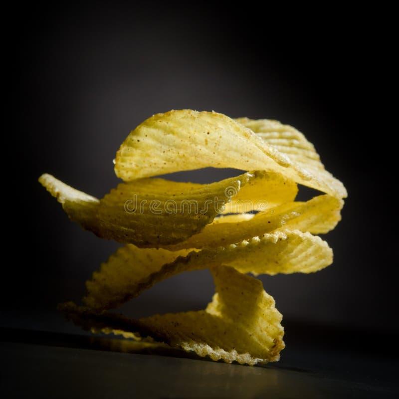 Potato Chips on Black Background royalty free stock photography