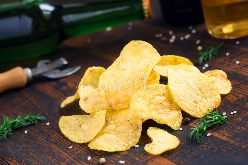 Potato Chips with dill on a background of beer bottles.  royalty free stock photography