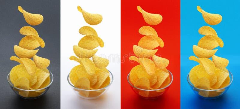 Potato chips falling into glass bowl isolated on white background, flying potato crisps stock images