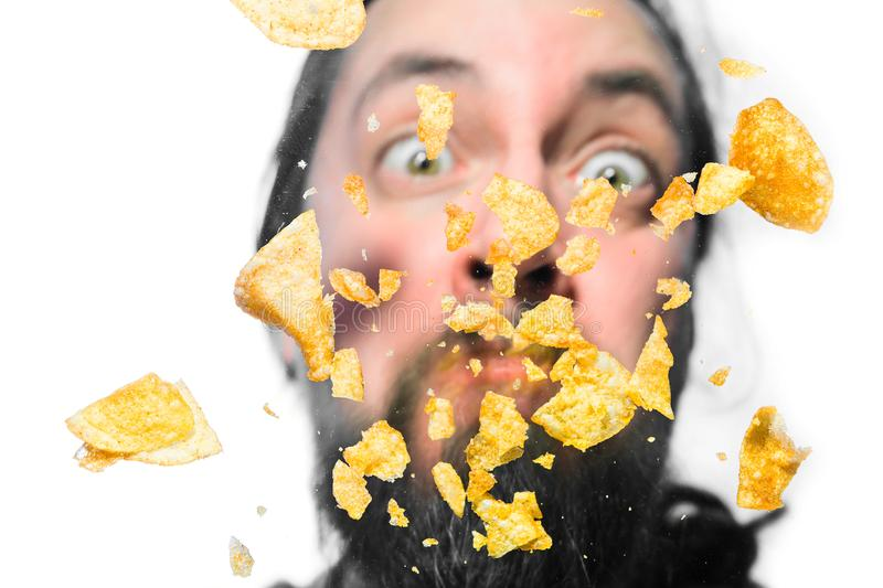 Potato chips on a pane. Mans face behind making grimace, from below shot royalty free stock images