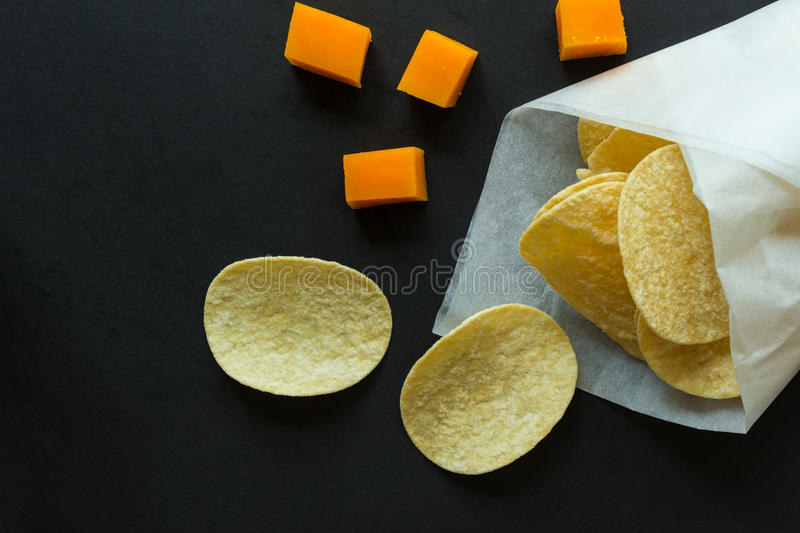Potato chips in a paper bag and cheese cubes royalty free stock photos