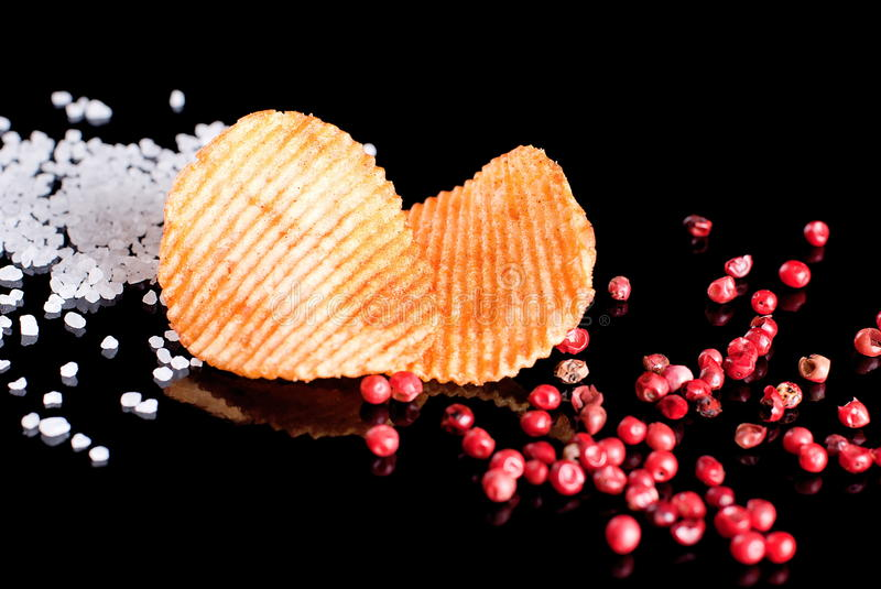 Potato chips with salt and hot peppers royalty free stock photography