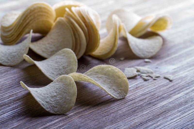 Potato chips. Several potato chips on woodena table stock photo