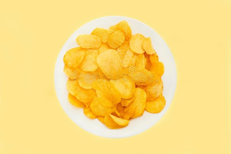 Potato chips in a white plate isolated on bright yellow background. Fast food. Top view stock image