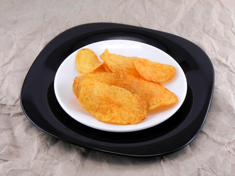 Potato chips in white plate on old paper. Tasty potato chips in white plate on old paper stock images