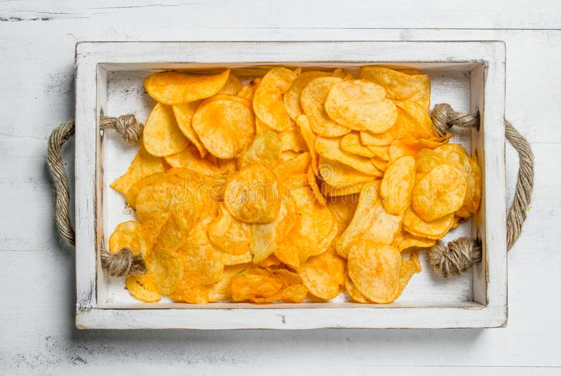 Potato chips in a wooden tray. On white rustic background stock image
