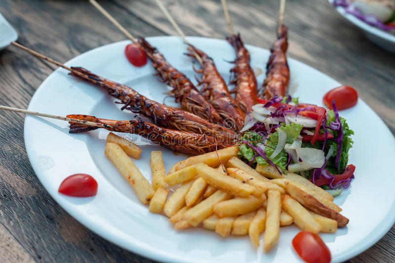 Potato fries with fry prawns, lettuce salad. over wooden background stock images