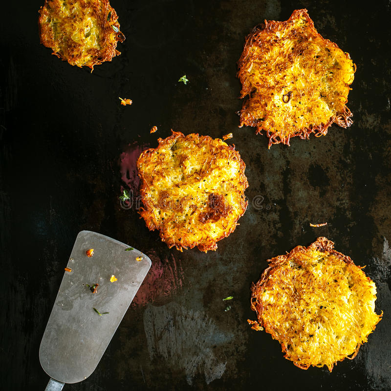 Potato fritters frying on a griddle royalty free stock photography