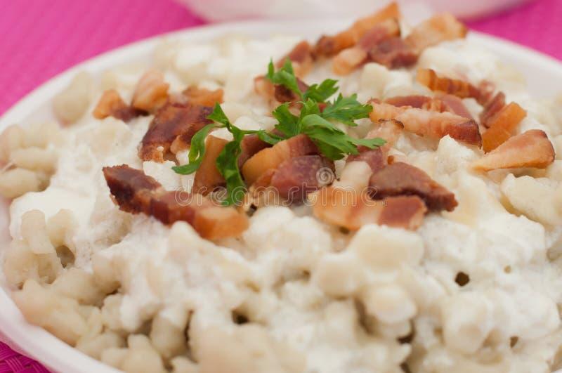 Potato gnocchi dumplings with sheep cheese and bacon. Slovak traditional food - potato gnocchi dumplings with sheep cheese and bacon stock photos