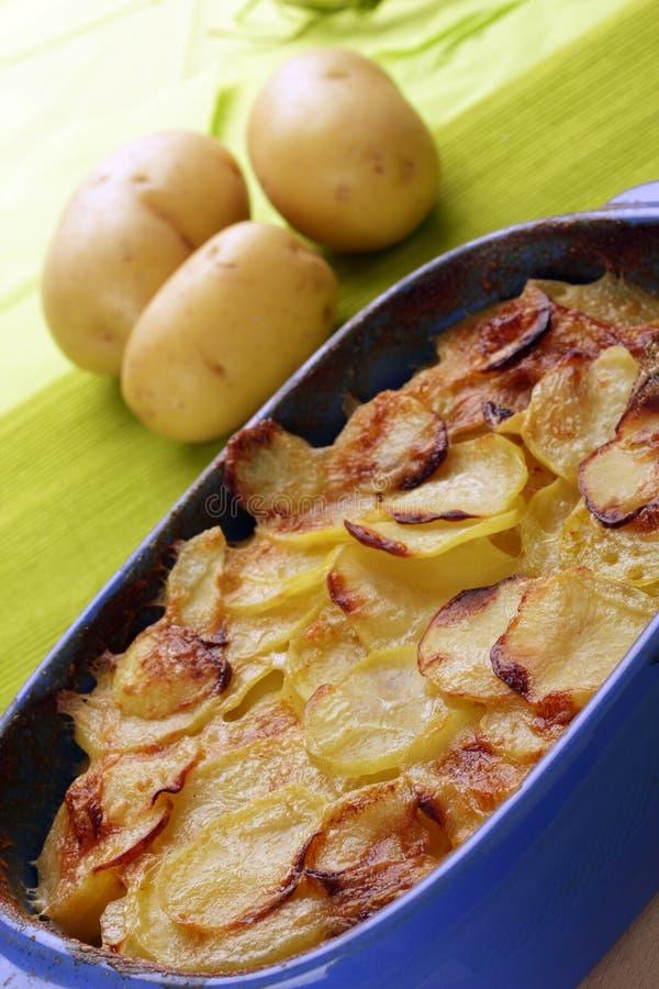 Potato gratin. Backed in a blue ceramic dish royalty free stock photos