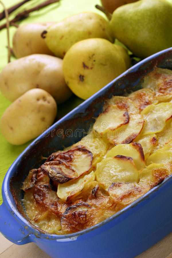 Potato gratin. Backed in a blue ceramic dish royalty free stock photography
