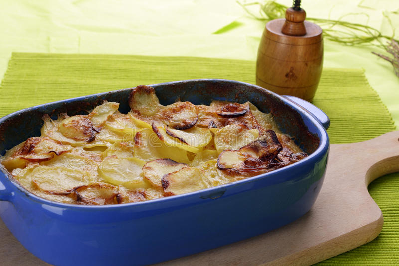Potato gratin. Backed in a blue ceramic dish royalty free stock photo