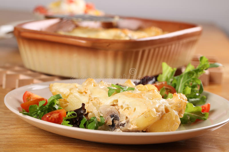 Potato gratin. With mushrooms, eggs, cheese and mixed greens stock images