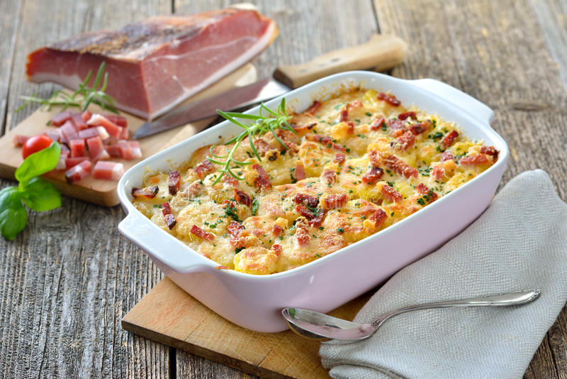 Potato gratin with bacon. Hearty potato gratin with parmesan cheese, cream and delicious cured bacon from South Tyrol freshly served from the oven stock photography