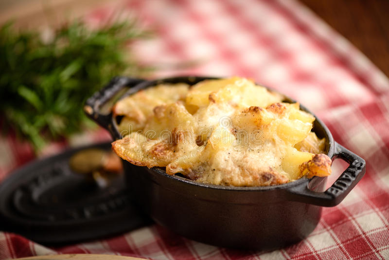 Potato gratin dauphinois. In traditional french ceramic pan on rustic tablecloth royalty free stock photos