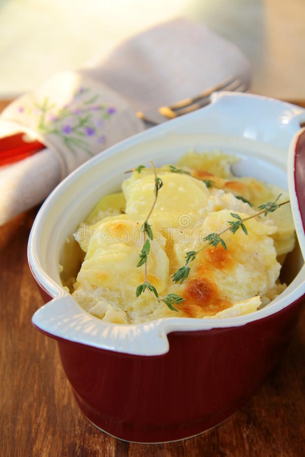 Potato gratin dauphinoise in the pan on rustic bac stock images