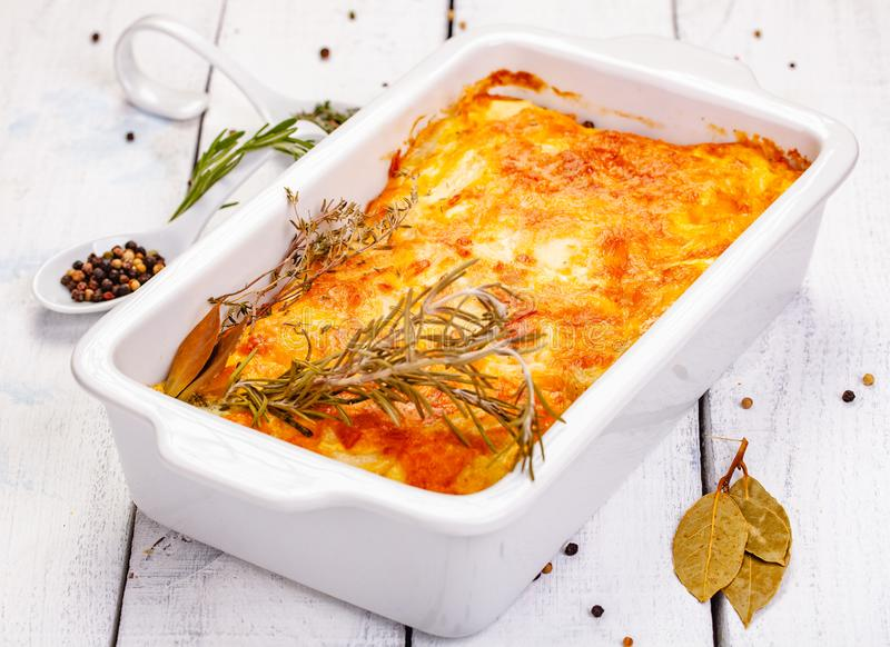 Potato gratin in white casserole dish on wooden rustic table. Close up stock photos