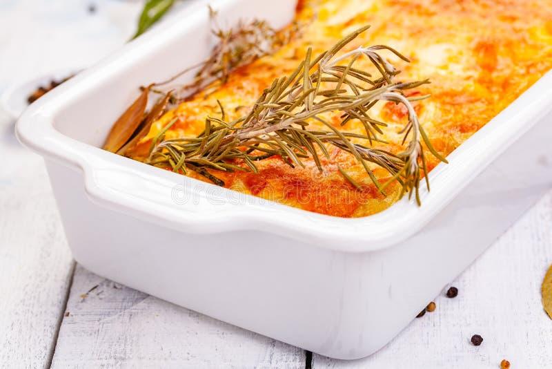 Potato gratin in white casserole dish on wooden rustic table. Close up stock photo