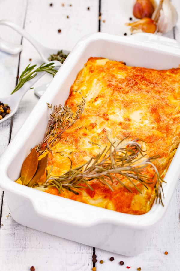 Potato gratin in white casserole dish on wooden rustic table. Close up royalty free stock image