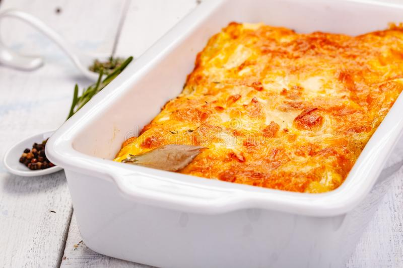 Potato gratin in white casserole dish on wooden rustic table. Close up stock photography
