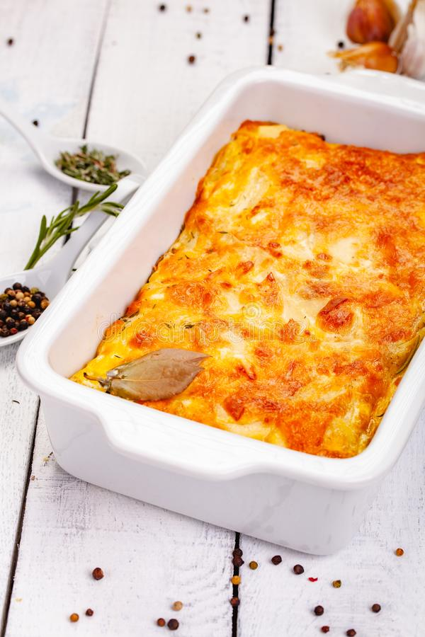 Potato gratin in white casserole dish on wooden rustic table. Close up royalty free stock photos