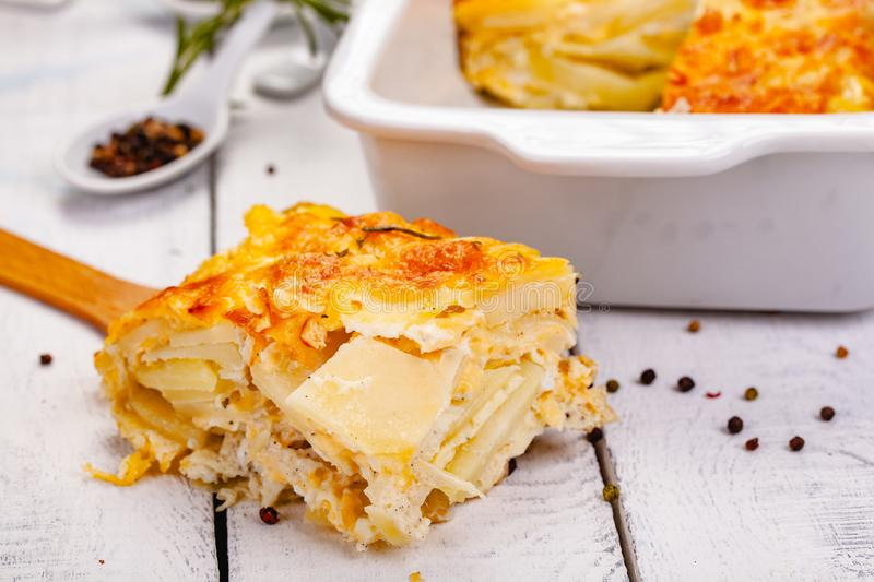 Potato gratin on wooden rustic table. Close up stock photography