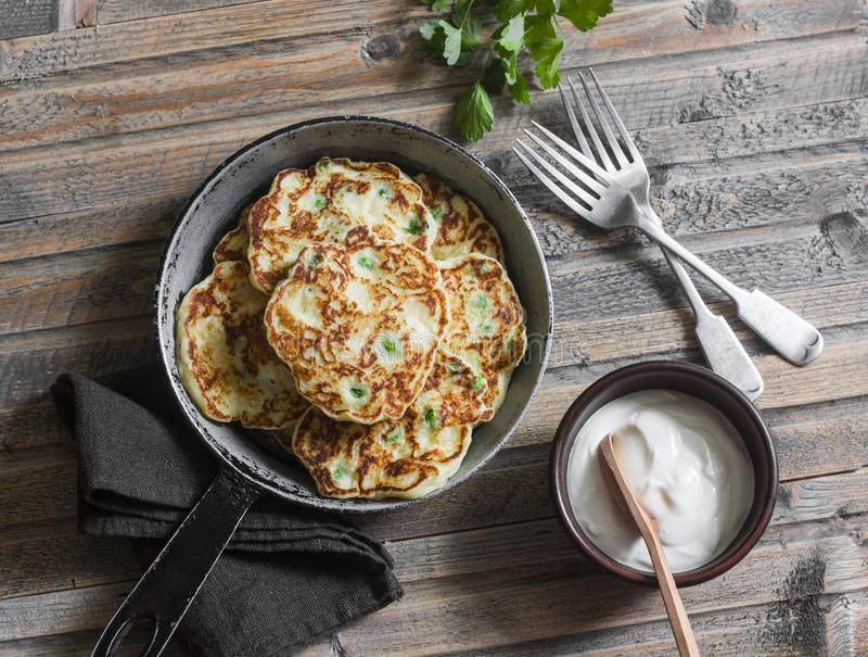 Potato, leek and green pea pancakes in the pan on wooden background, top view. Simple rustic food royalty free stock photo