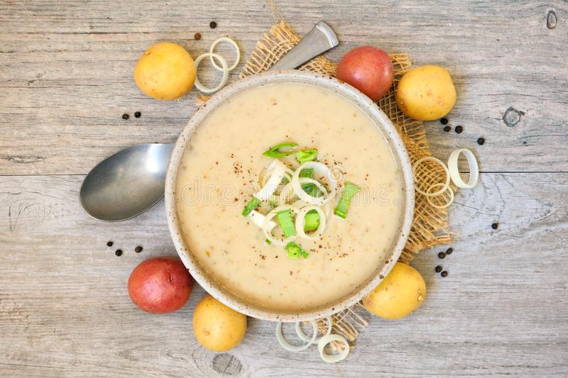 Potato and leek soup, above view on light brown wood royalty free stock images
