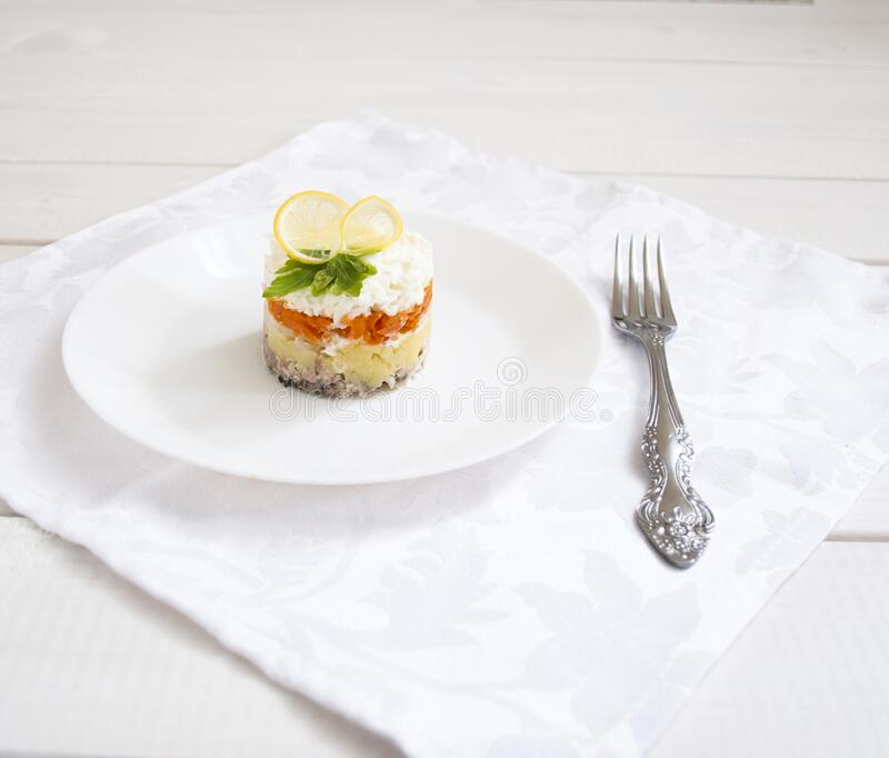Potato mimosa salad with carrot layers on a white wooden table royalty free stock photography