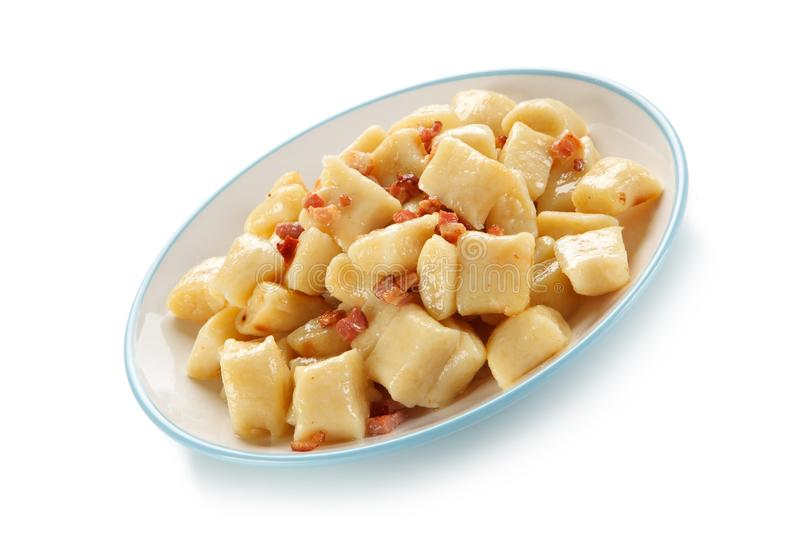 Potato noodles - dumplings with bacon. On white background royalty free stock image